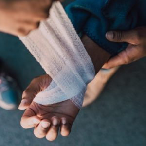 person putting bandage on another person s hand